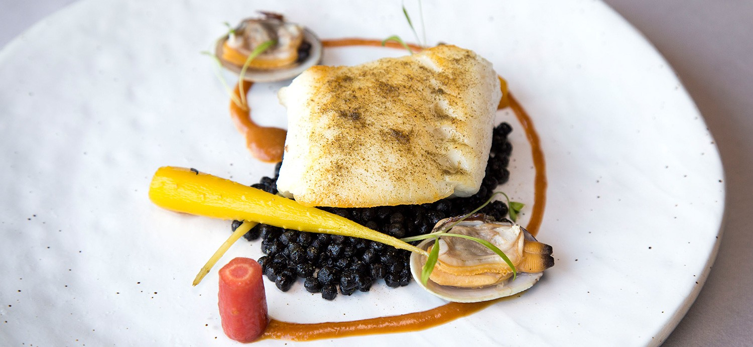 Miso glazed snow fish, black ink fregola sarda, manila clams, and heirloom carrots